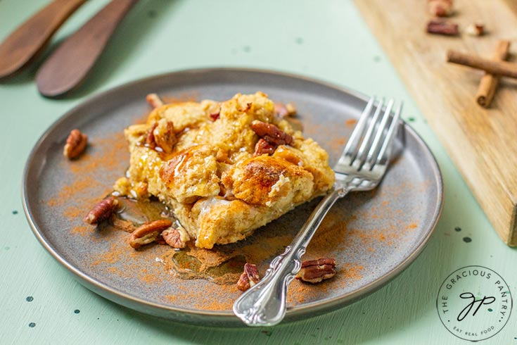 A slice of this Pumpkin Spice French Toast Casserole Recipe sits on a plate with a fork, ready to enjoy for breakfast.