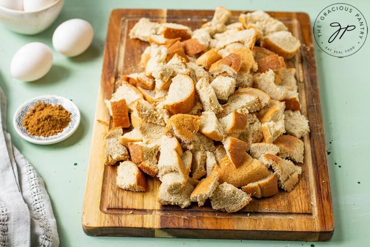 The whole grain bread lays on a cutting board, cut into little, bite-sized pieces.