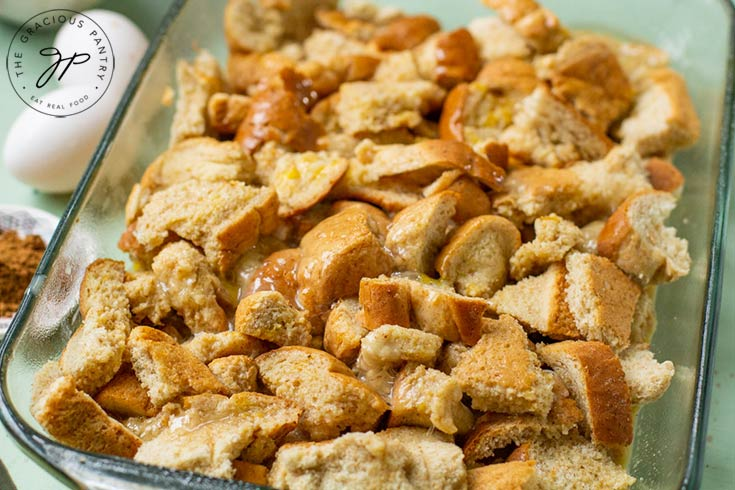 Bread sits in casserole dish with egg mixture poured over it, ready to bake.