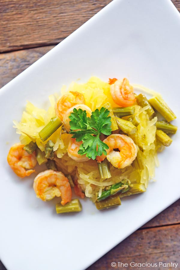 Clean Eating Shrimp And Asparagus Spaghetti Squash Spaghetti shown from overhead and served on a rectangular white plate. You can see the shrimp laying over the shredded spaghetti squash.