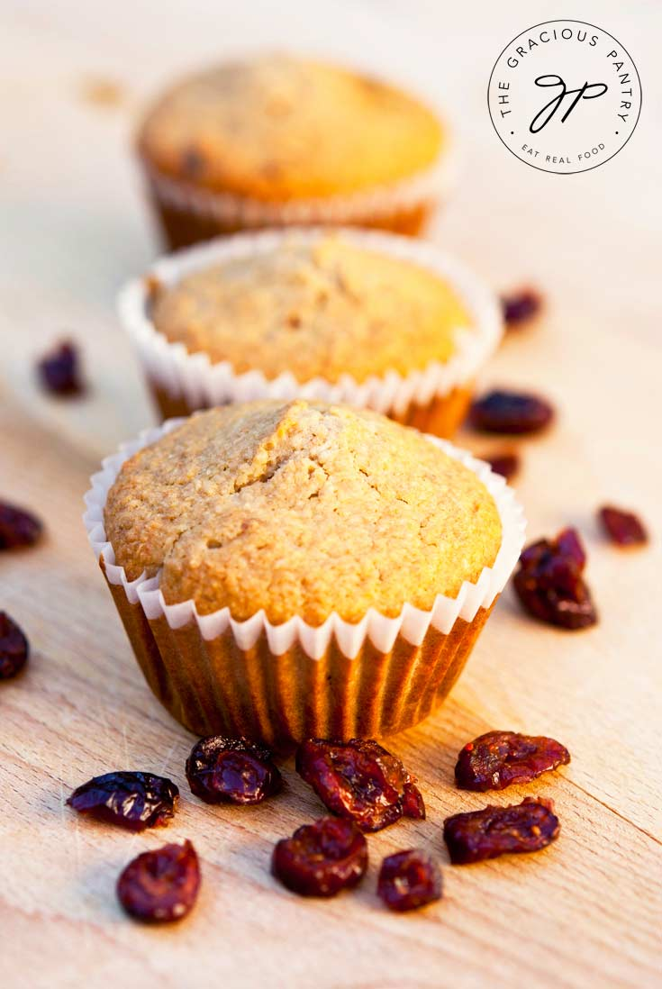 Three Clean Eating Cranberry Oat Bran Muffins are lined up on a wooden surface. They have golden brown tops and are in white cupcake liners.