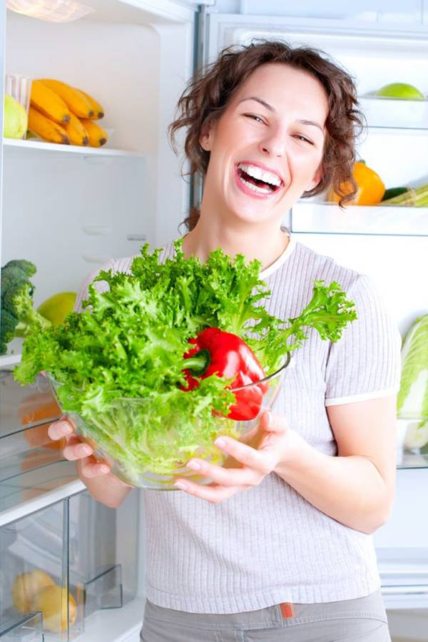 Achieve Your Health Goals? Is this the year? Woman smiles as she stands in front of the fridge holding a glass bowl with a head of lettuce and red bell pepper in it.