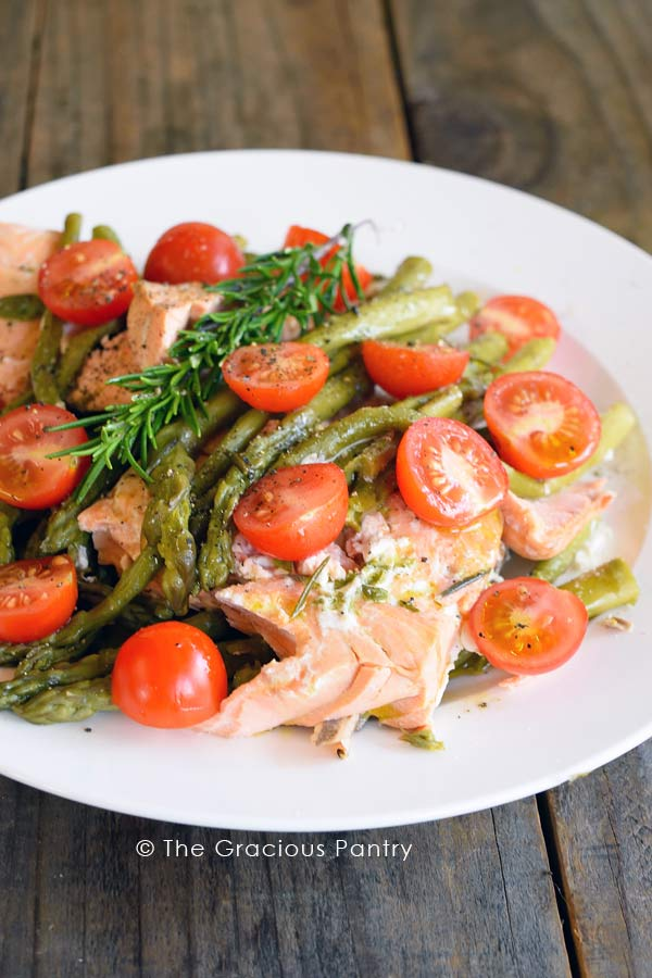 Clean Eating Pressure Cooker Mediterranean Rosemary Salmon broken into pieces and topped with asparagus, cherry tomatoes, a sprig of fresh rosemary and finally drizzled with a bit of fresh olive oil.
