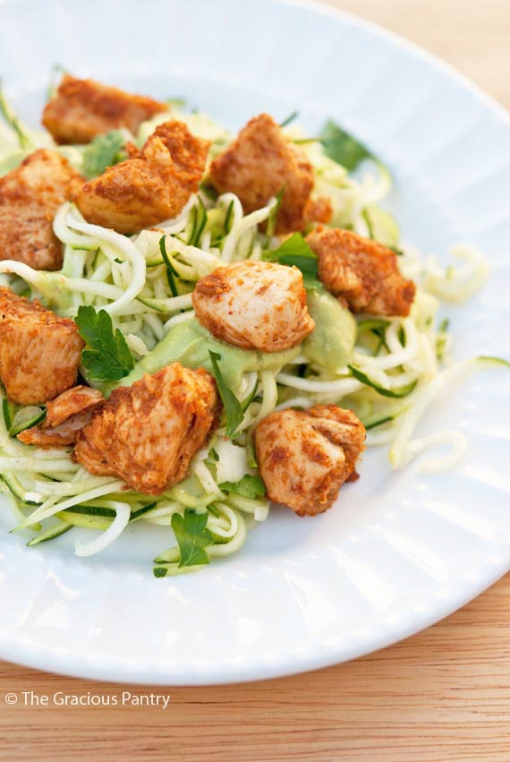 Clean Eating Taco Chicken Zucchini Pasta piled onto a white plate. The zucchini pasta is a bright green and the chunks of chicken are a golden brown color.