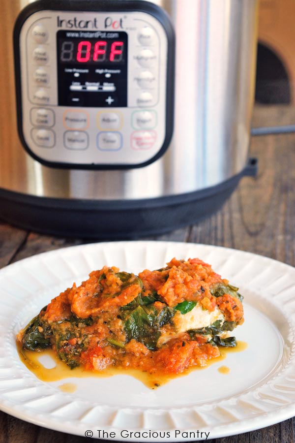 A single white plate holding this Clean Eating Instant Pot Spinach Chicken sits in front of an Instant Pot.