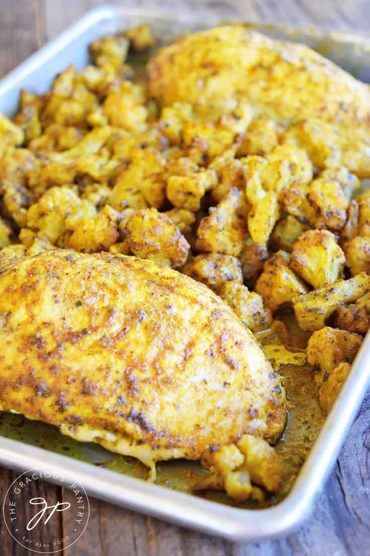 Clean Eating Sheet Pan Chicken And Cauliflower recipe on the sheet pan it was cooked on.