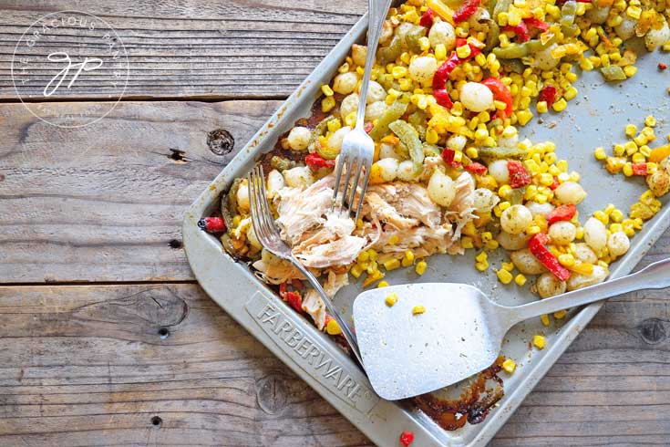 This Clean Eating Sheet Pan Mexican Chicken Dinner Recipe can also be shredded for taco filling. This image shows the chicken already shredded and still laying next to the vegetable on the sheet pan.