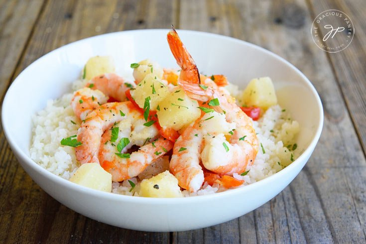 Clean Eating Sheet Pan Pineapple Shrimp Recipe in a white bowl, fresh out of the oven and ready to eat.