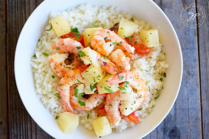 Clean Eating Sheet Pan Pineapple Shrimp Recipe shown from overhead. Presented in a white bowl and showing the entire dish of shrimp, pineapple chunks and green garnish over a bed of riced cauliflower.