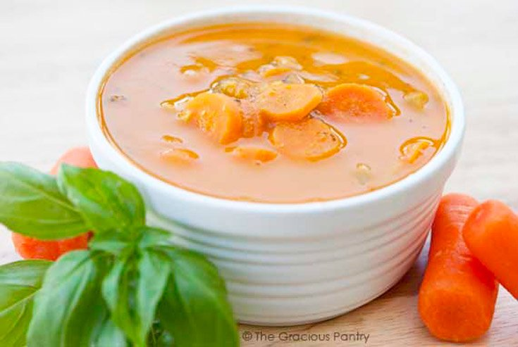 A white bowl filled with an orange/red soup. Carrots lay to the side of the bowl.
