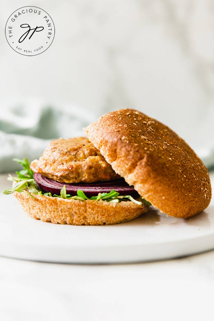 One of a batch of these Clean Eating Baked Turkey Burgers sits on a whole-grain bun, with the top bun sitting off to the side. You can see the meat patty sitting on a slice of red onion and bed of green lettuce.