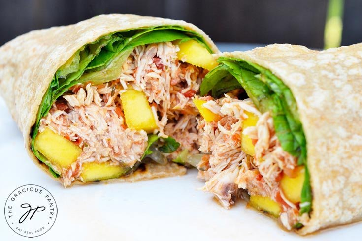 This Clean Eating Mango Chicken Wrap cut in half and ready to sink your teeth into