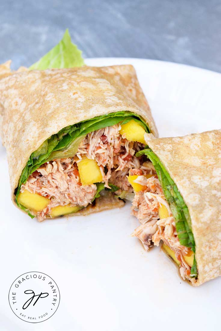 A delicious Clean Eating Mango Chicken Wrap Cut In Half And Served On A Plate
