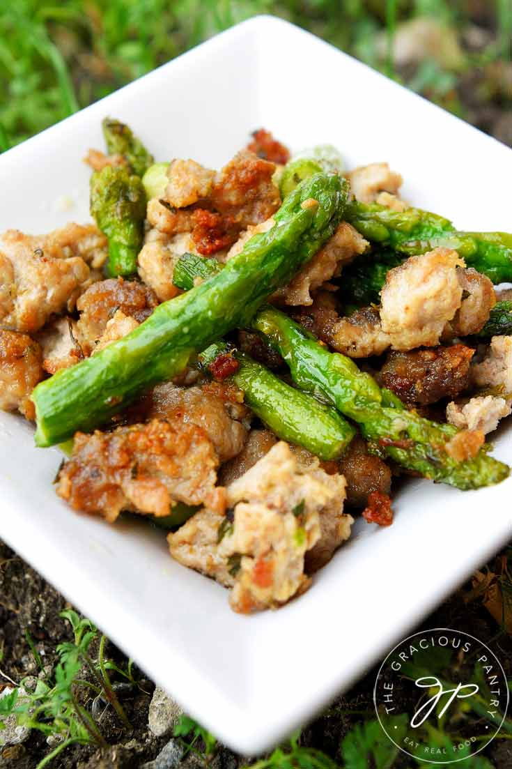 Clean Eating Ground Turkey Asparagus Skillet shown up close in a white dish. You see the scrambled, ground turkey and pieces of asparagus.