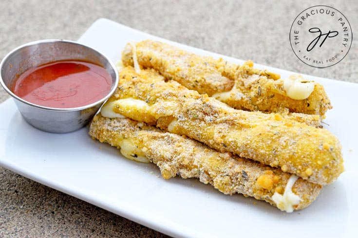 Clean Eating Air Fryer Cheese Sticks served on a white, rectangular plate with a small metal dish of marinara along side it.