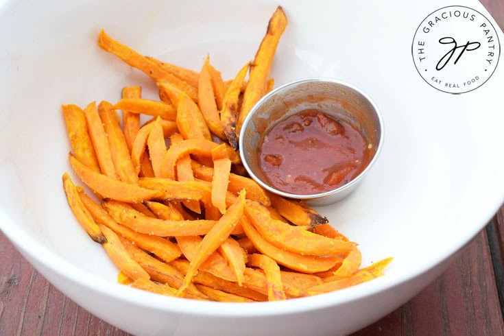 An overhead view of a white bowl filled with Clean Eating Air Fryer Garlic Sweet Potato Fries and a small dish of red sauce nestled next to them.