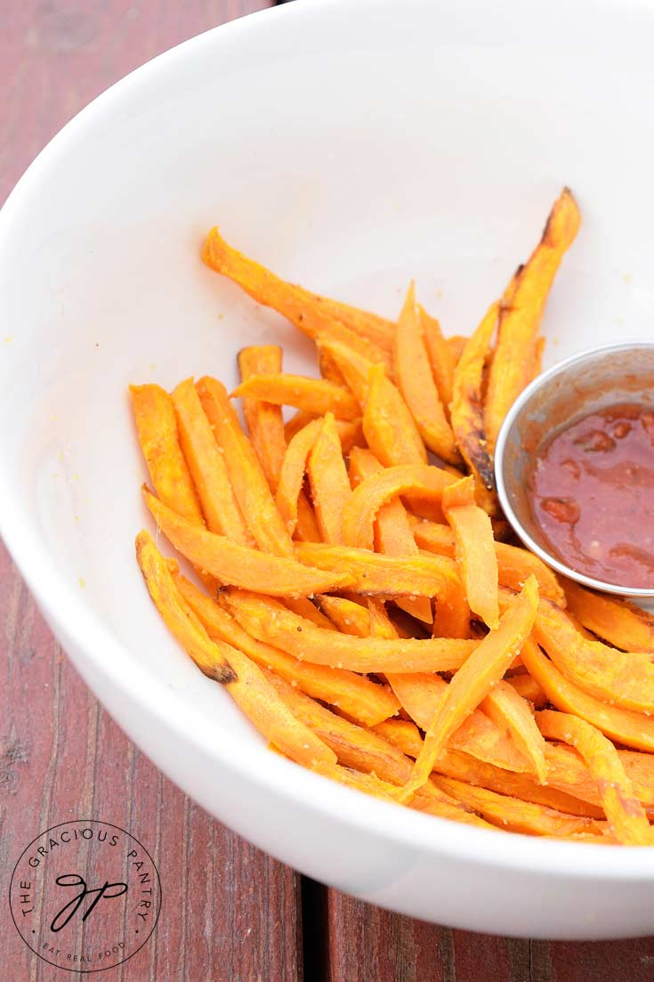 Bright orange, Clean Eating Air Fryer Garlic Sweet Potato Fries in a large white bowl with a small dish of mariner next to them.