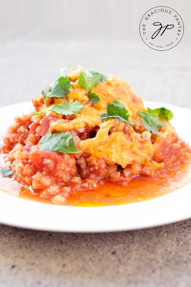 Clean Eating Cheesy Mexican Chicken Casserole Recipe heaped on a white plate with melting cheddar oozing down the sides and topped with chopped cilantro.
