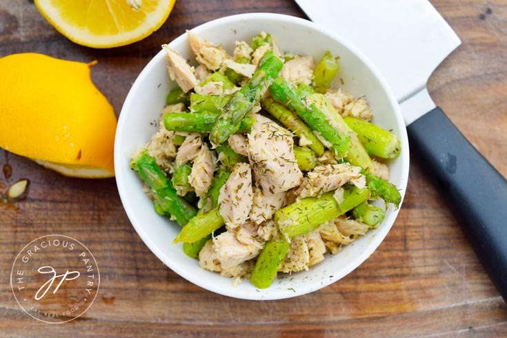 Overhead shot of a white bowl filled with this Clean Eating Tuna Asparagus Skillet recipe which contains asparagus, tuna, dill and more.