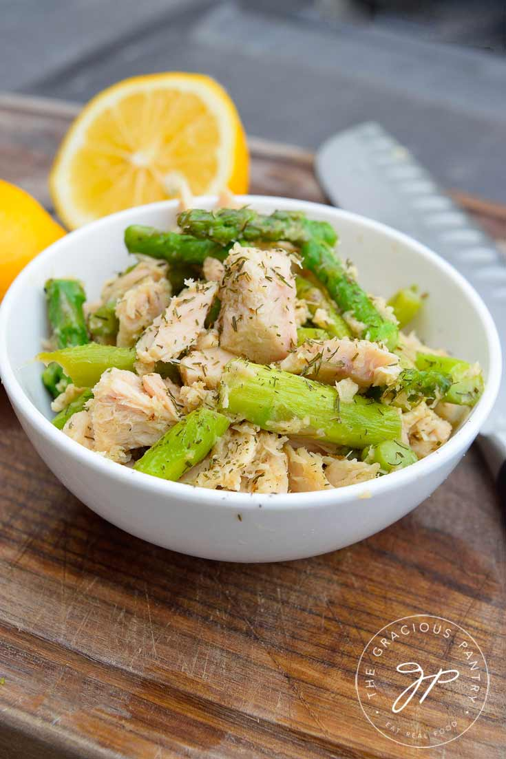 Clean Eating Tuna Asparagus Skillet recipe presented in a white bowl on top of a cutting board with lemon wedges next to the bowl.