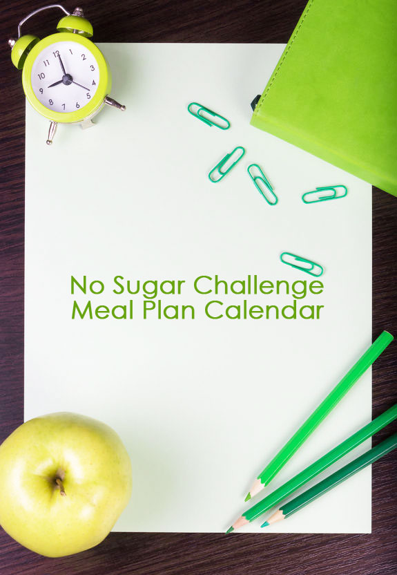 A piece of paper with the words, No Sugar Challenge Meal Plan Calendar written across it. There is a small clock, a green apple, and some green paper clips laying around the border of the paper.