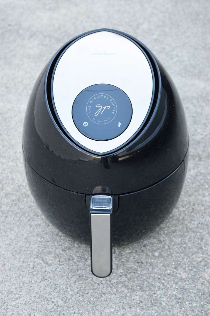 Modern Home Air Fryer on gray, cement background showing the air fryer with it's drawer closed.