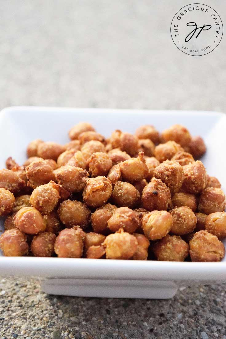 Clean Eating Air Fryer Roasted Chickpeas shown in a square, white bowl. The chickpeas are roasted to a golden brown color and look delicious and ready to eat!