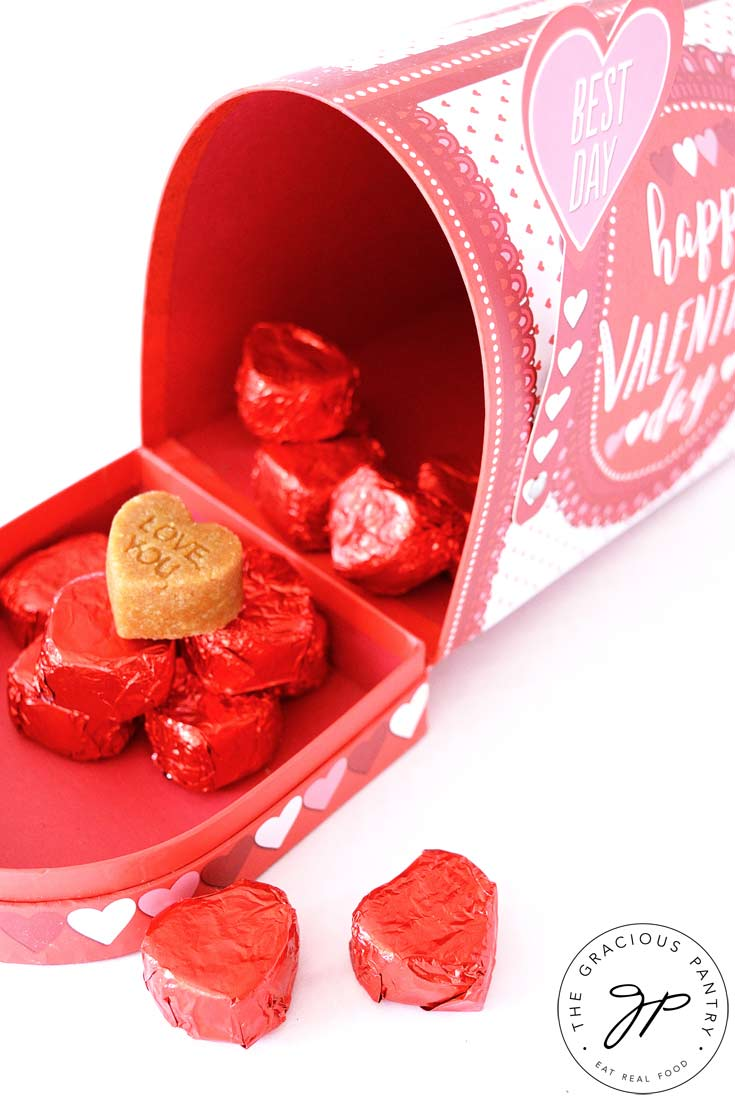 Clean Eating Marzipan Candy wrapped in red foils and displayed in and around a small, decorative Valentine's Day mailbox with the lid open.