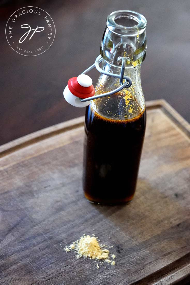Clean Eating Teriyaki Sauce in a glass bottle with the lid open. You can see a few ginger specks on the side of the bottle from when the sauce was pour into it. There is a small sprinkle of ginger next to the bottle as well.