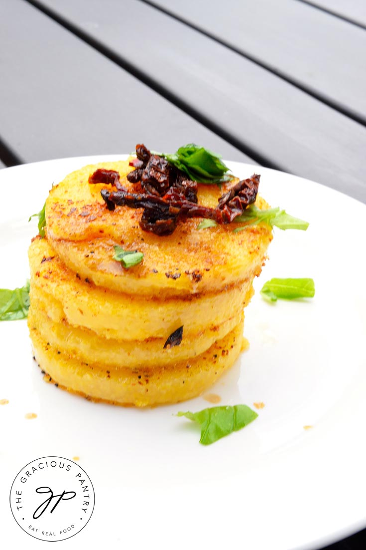 A stack of Clean Eating Italian Polenta Rounds piled high on a round, white plate. The stack is topped with chopped sun dried tomatoes and bits of fresh basil. It almost looks like a stack of cookies!