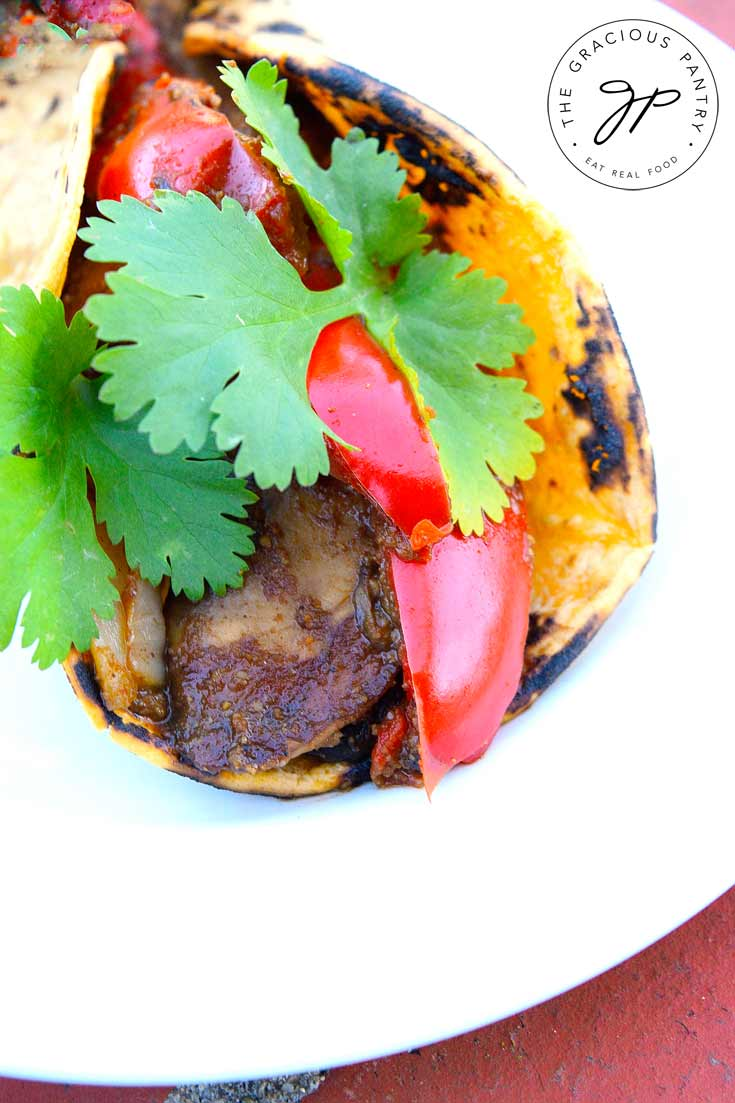 A Clean Eating Portobello Mushroom Taco sits on a white plate. You can see folded tortilla filled with cooked mushrooms and bright, red bell peppers. The taco has a tiny bit of fresh, green cilantro for garnish.