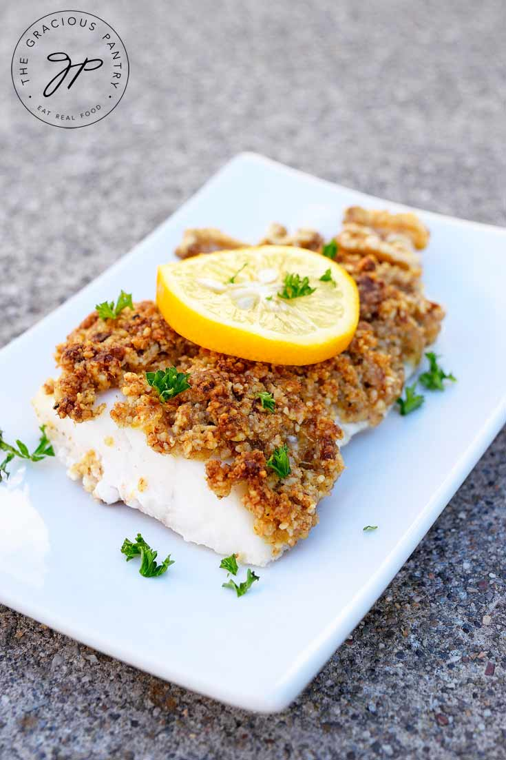 A white plate holds a fillet of Clean Eating Walnut Crusted Cod. It has a slice of lemon on top and is sprinkled with bits of fresh parsley.