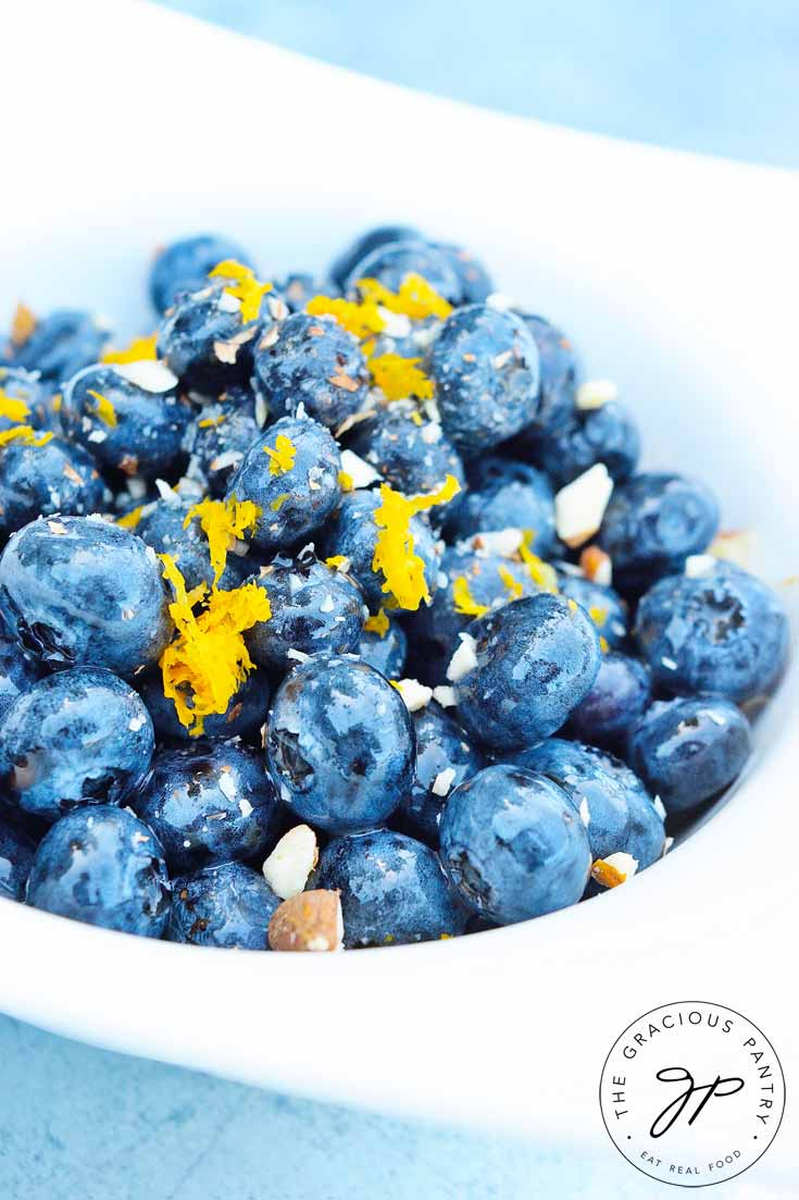An up close shot of this Clean Eating Almond Blueberry Salad in a white bowl. The blueberries are a vibrant blue and have little bits of almonds and lemon zest sprinkled across the top.