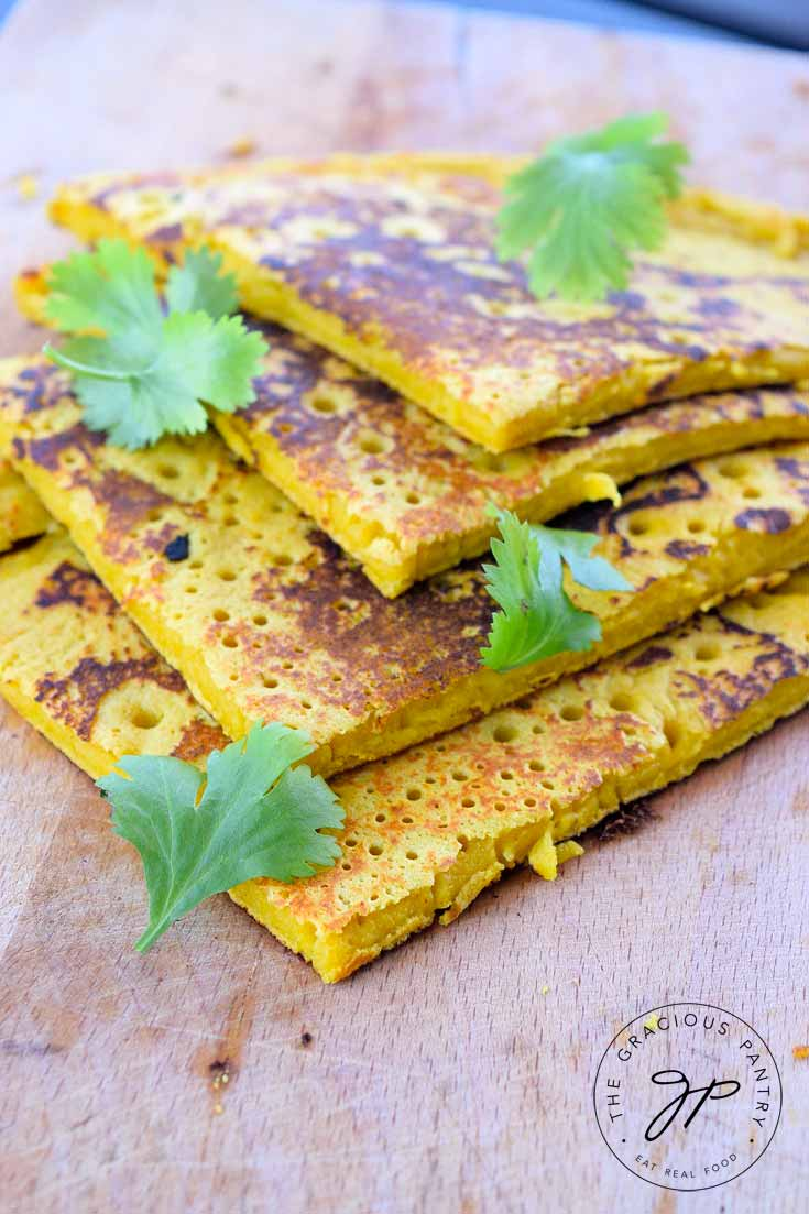 Clean Eating Chickpea Flour Flatbread cut into 4 pieces and layers on a cutting board. There are a few sprigs of fresh herbs sprinkled over the top.