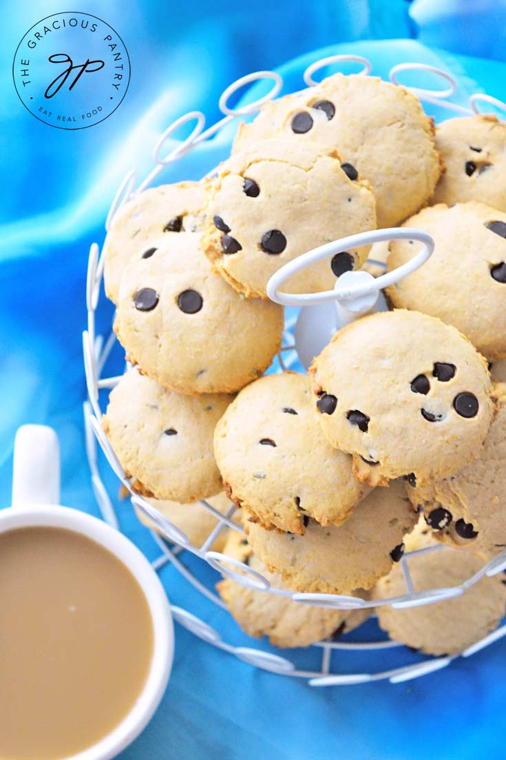 A two tiered platter holds an entire batch of Clean Eating Lavender Chocolate Chip Tea Biscuits. A cup of coffee sits next to the platter.