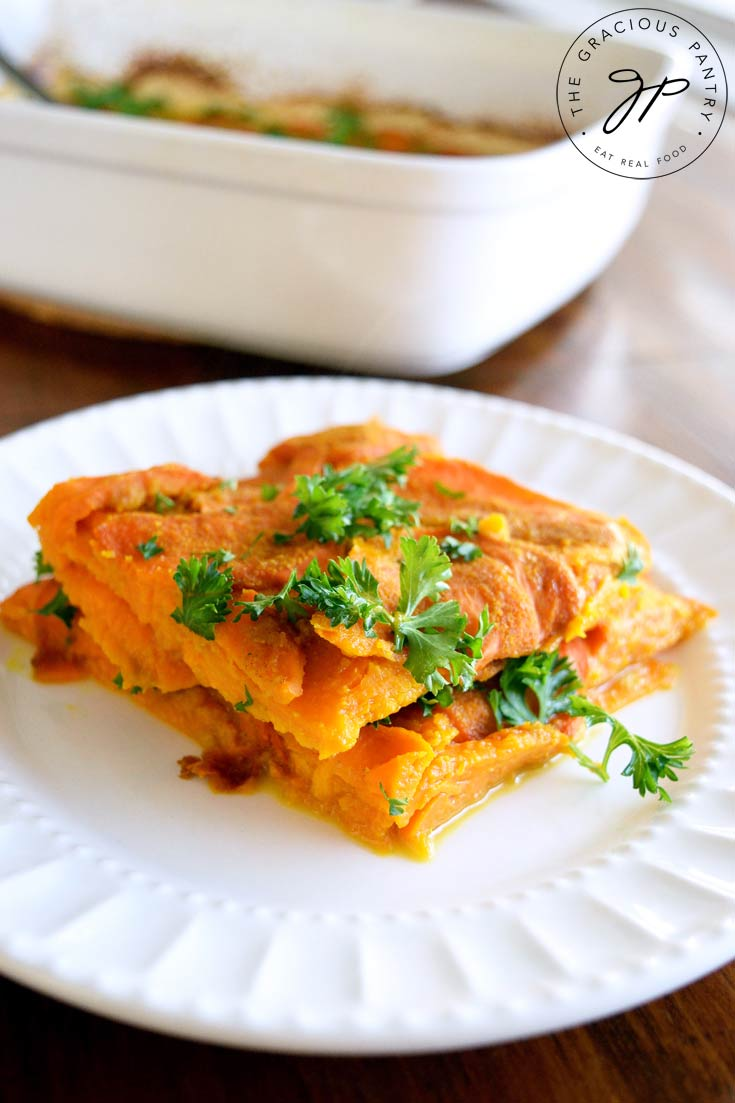 A white plate sits on a wooden table in front of a white casserole dish that this Clean Eating Layered Sweet Potato Casserole was baked in. It has a serving of the potatoes on the plate with fresh parsley sprinkled over the top for garnish.