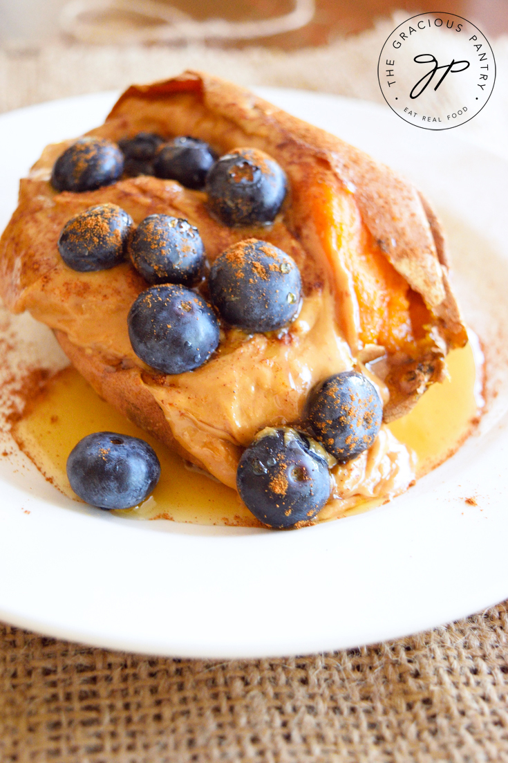 A closeup view of this Clean Eating Loaded Breakfast Sweet Potato shows just a hint of the orange flesh of the sweet potato peaking out from under a layer of creamy peanut butter topped with fresh, ripe blueberries. You can see the drizzle of maple syrup beginning to pool on the plate under the potato as well.