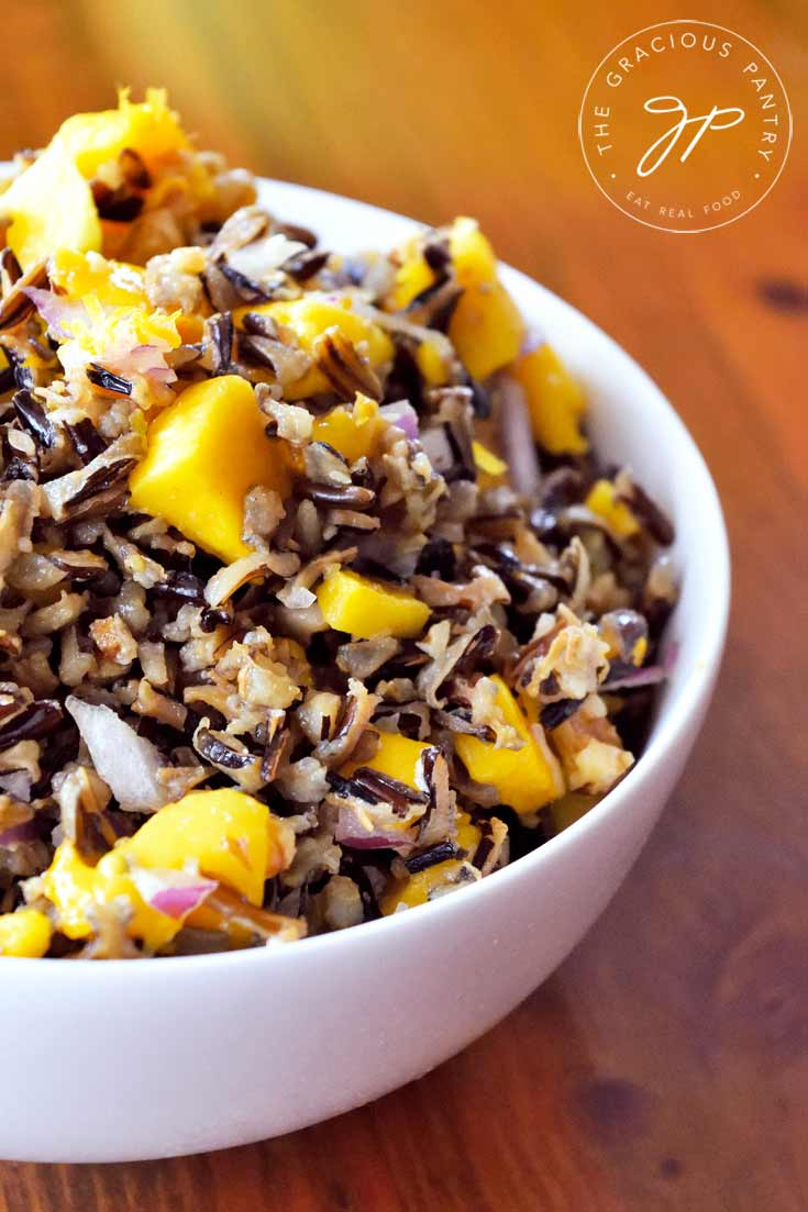 A close up shot of a white bowl filled with Clean Eating Mango Wild Rice Salad. The bowl sits off to the left side of the photo so you can see about half of the bowl.