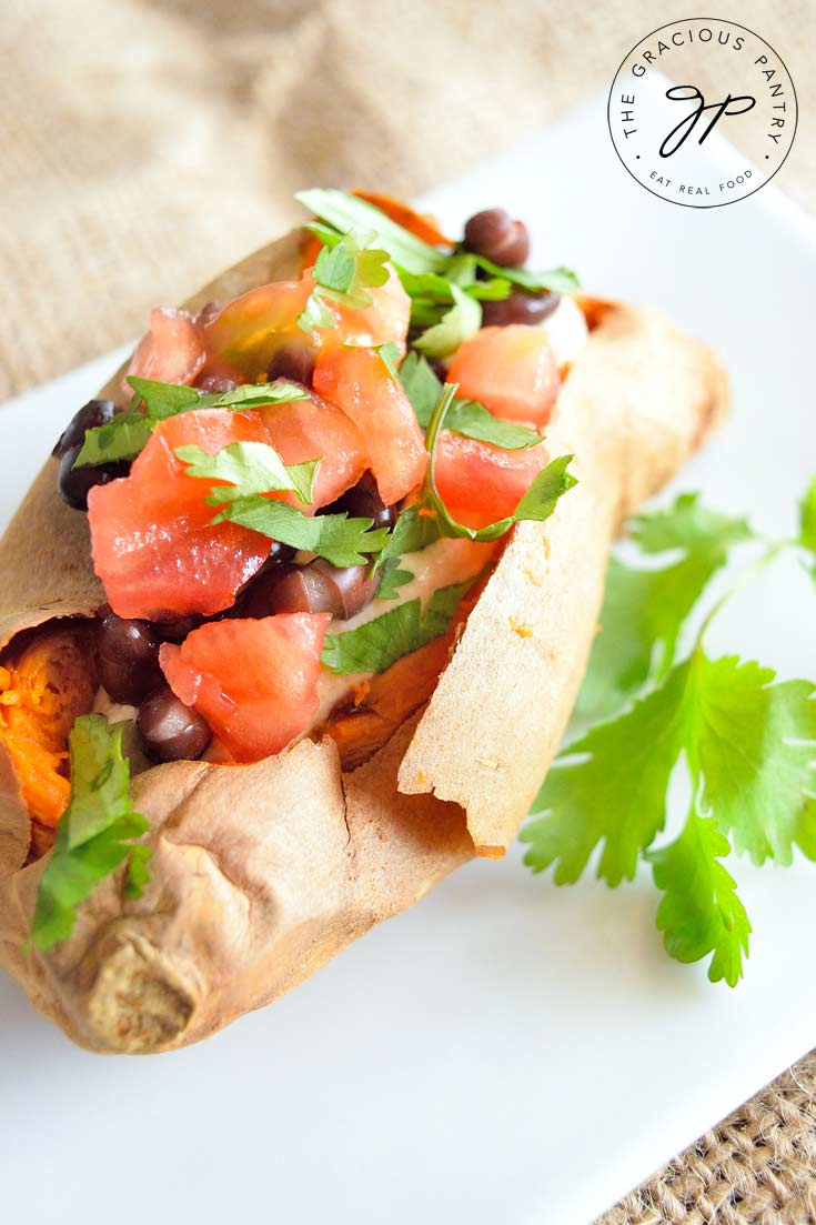 A Clean Eating Southwestern Stuffed Sweet Potato sits on a white plate with a sprig of fresh cilantro next to it. You can see the layers of ingredients starting with the sweet potato, then the hummus, black beans and finally, the tomatoes and cilantro.