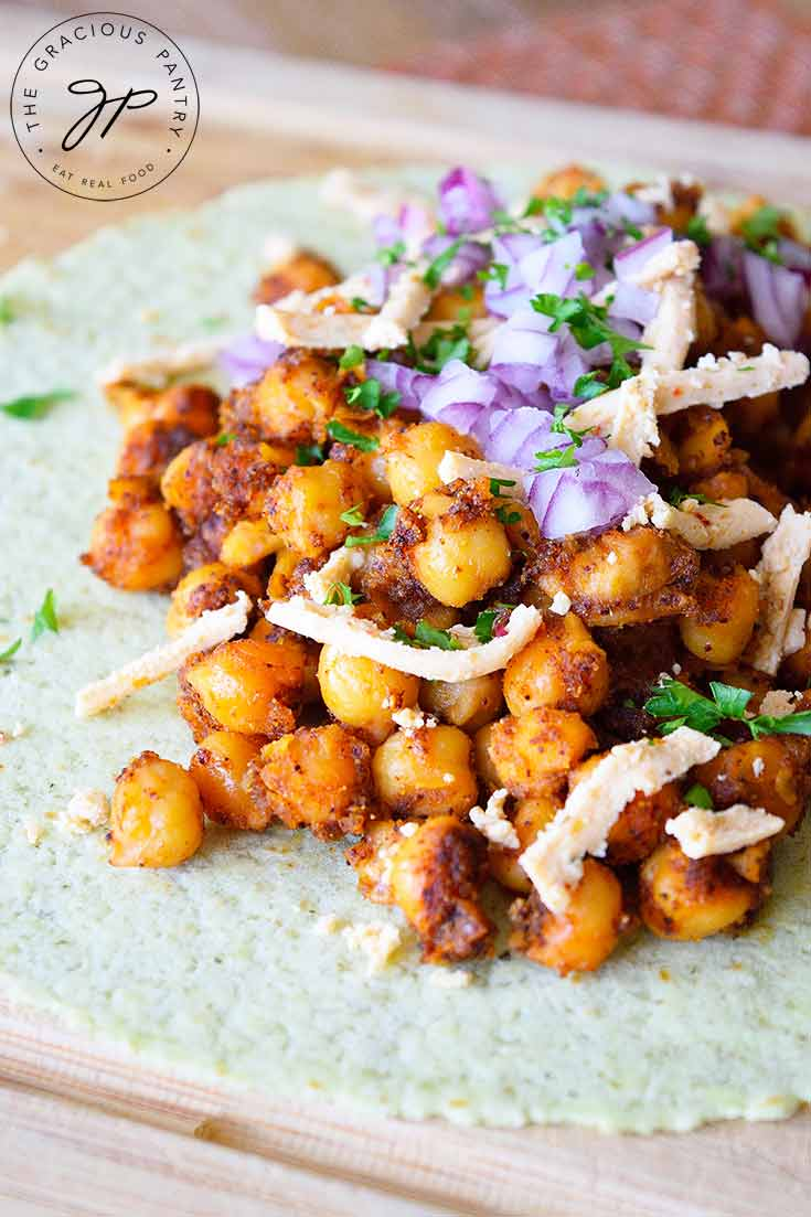 A flat tortilla sits on a cutting board layered with seasoned chickpeas, shredded cheese and chopped, purple onions in this Chickpea Tacos Recipe