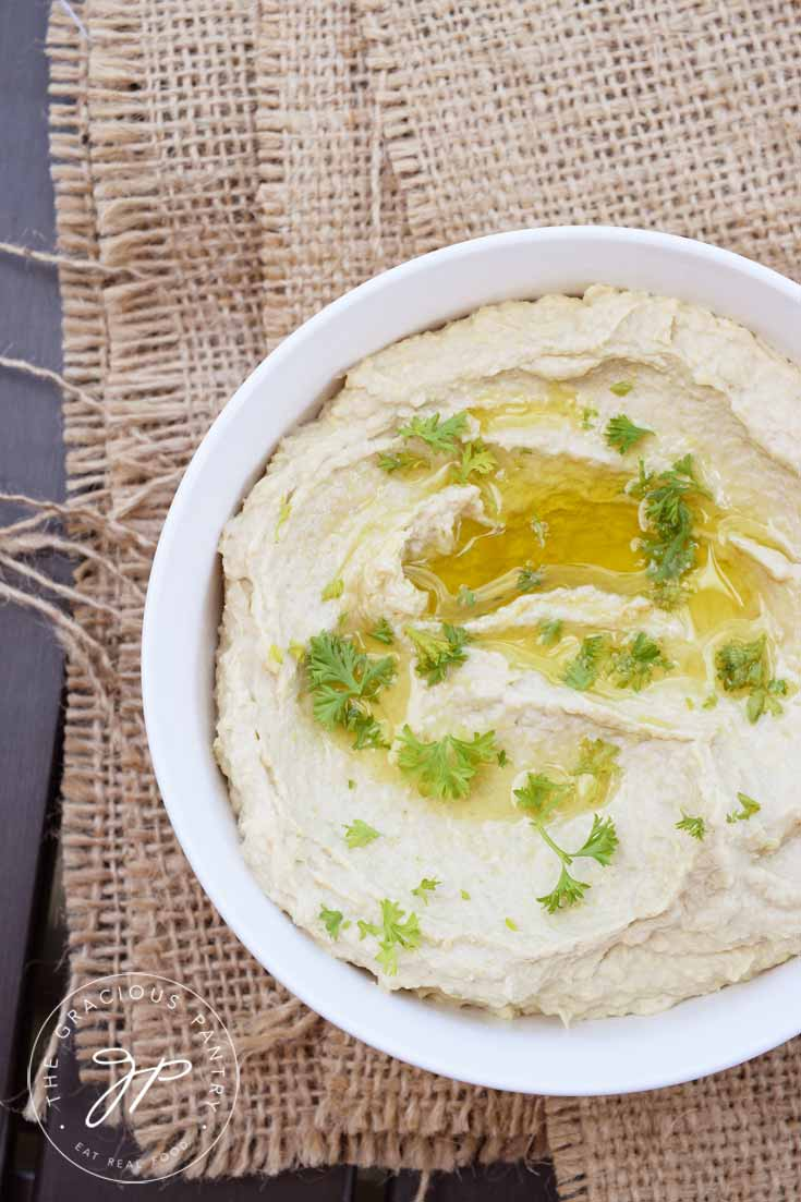 A white, round bowl sits on a piece of folded burlap on a wooden table. The view looks down into the bowl from overhead. There is olive oil drizzled over the top of the Clean Eating Artichoke Heart Hummus and there are a few sprinkles of fresh, chopped parsley over the top.