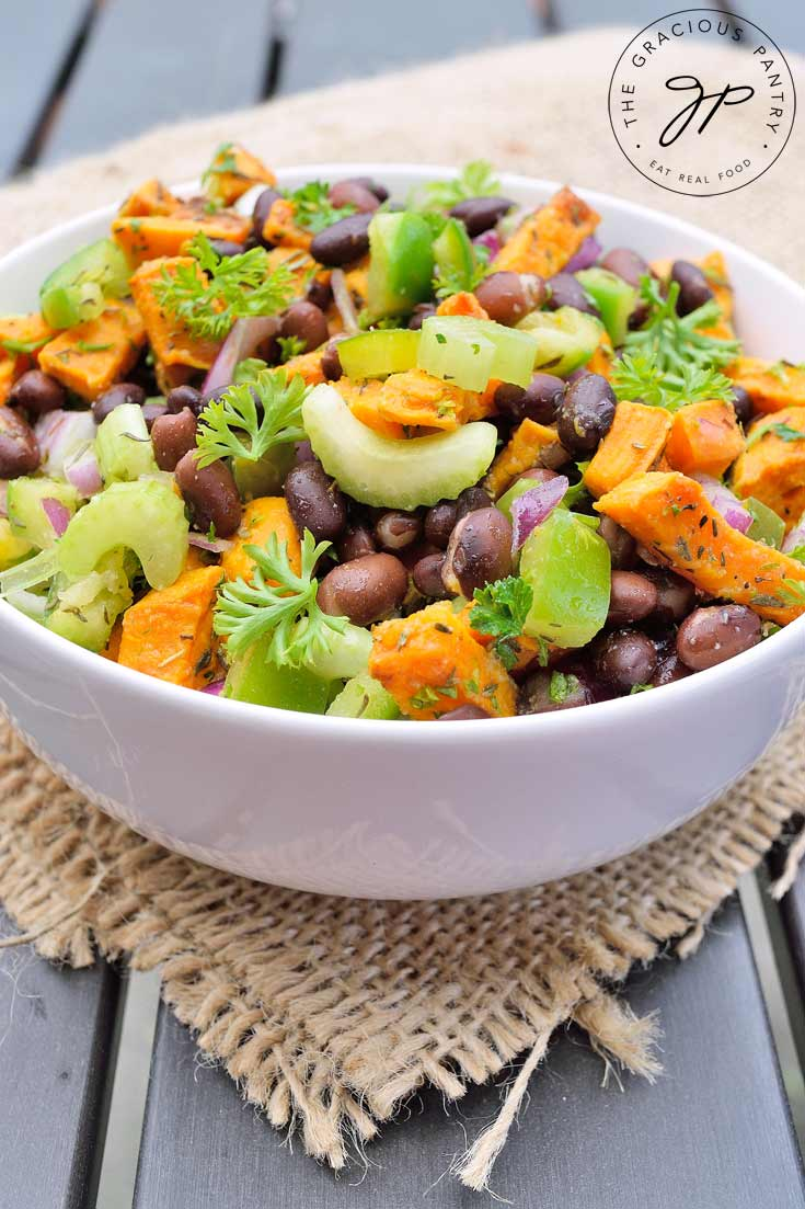 A white bowl on a dark wood table sits filled with Clean Eating Black Bean Roasted Sweet Potato Salad. You can see the beans, chunks of bright orange sweet potatoes and light green celery slices. It's topped off with chopped parsley.