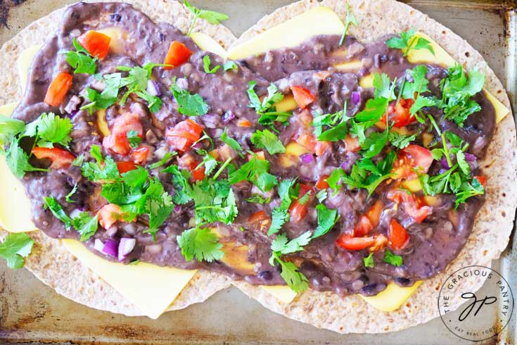 And overhead shot of this Clean Eating Loaded Sheet Pan Quesadillas shows the recipe just before the top layer of tortilla has been added. You can see the refried beans, tomatoes, onions and cilantro spread beautifully around the surface of the bottom layer of tortillas.
