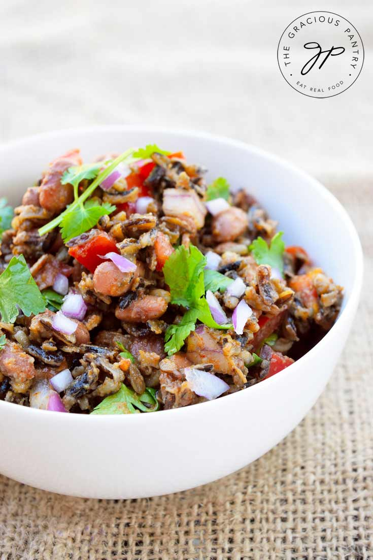 A white bowl filled with this Clean Eating Mexican Wild Rice Salad sits on a tan piece of burlap. In the bowl, you can see the rice mixed with bright red peppers, purple onions and bright green cilantro.