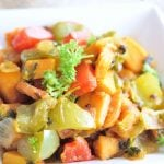 Sweet Potatoes O Brien in a square, white dish with chunks of sweet potatoes, green, and red bell peppers