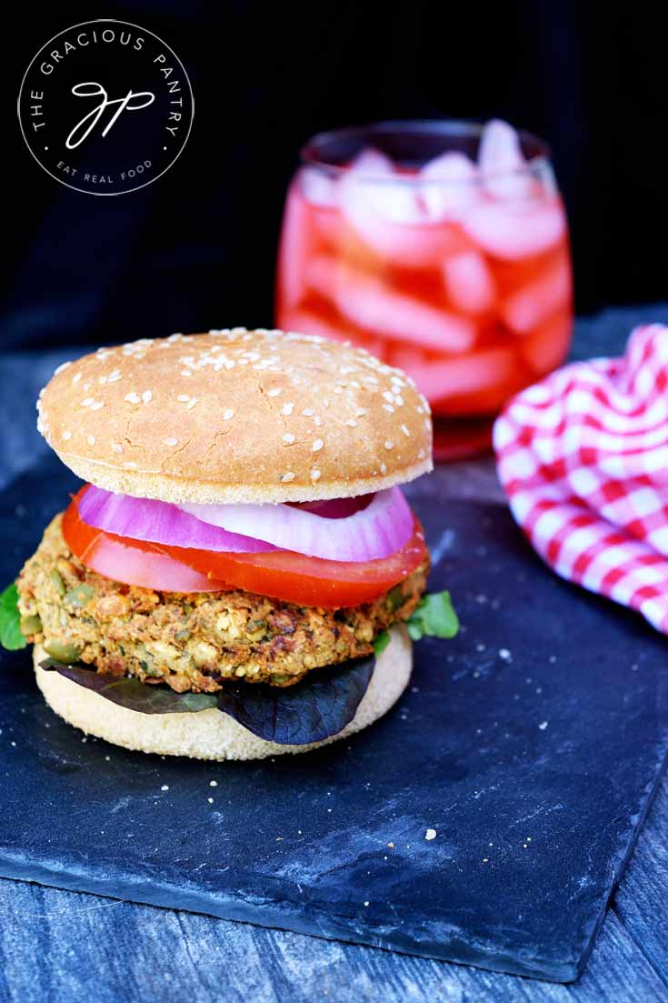 A straight on shot of one of these Clean Eating Chickpea Burgers shows the burger with a glass of red iced tea in a stemless wine glass sitting behind it and a red and white checkered napkin sitting to the right side of the burger.
