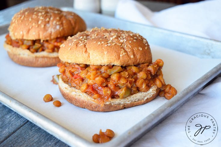 A second view of these Clean Eating Lentil Sloppy Joes better shows both sandwiches, one behind the other. You can see the lentils with bits of pepper throughout, in between the whole grain burger buns.