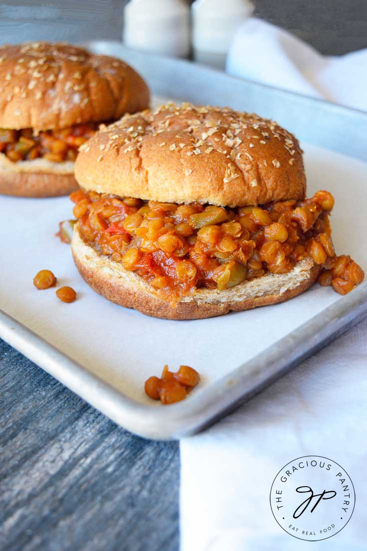 Two Clean Eating Lentil Sloppy Joes sit on a parchment-lined cookie sheet with a white towel next to it and a salt and pepper shaker in the background.