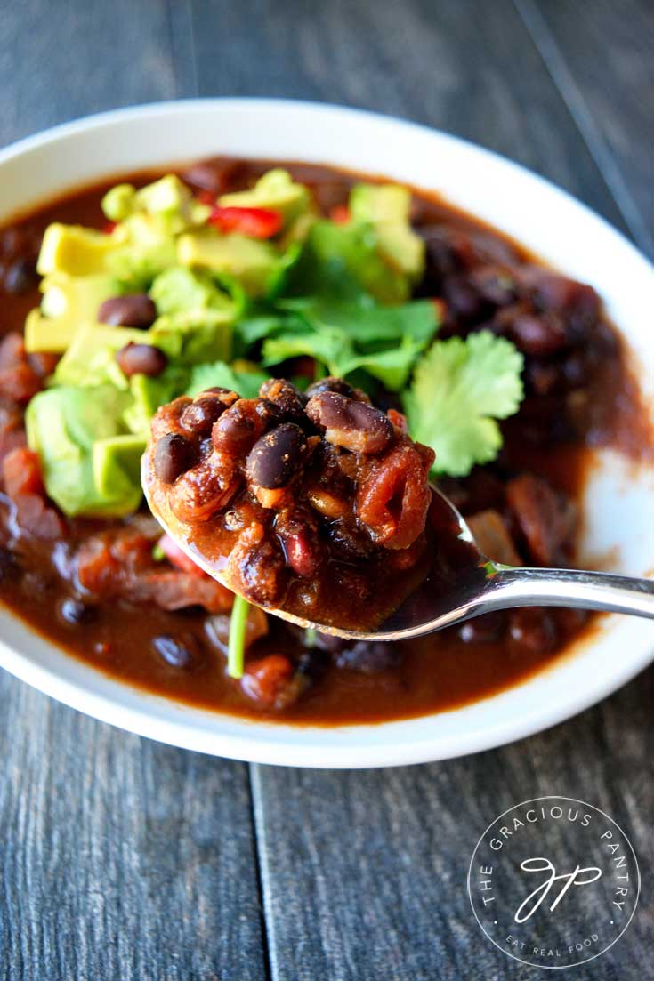 A white bowl of this Clean Eating Mexican Black Bean Chili sits in the background and a spoonful of it sits at the forefront, ready to take a bite.