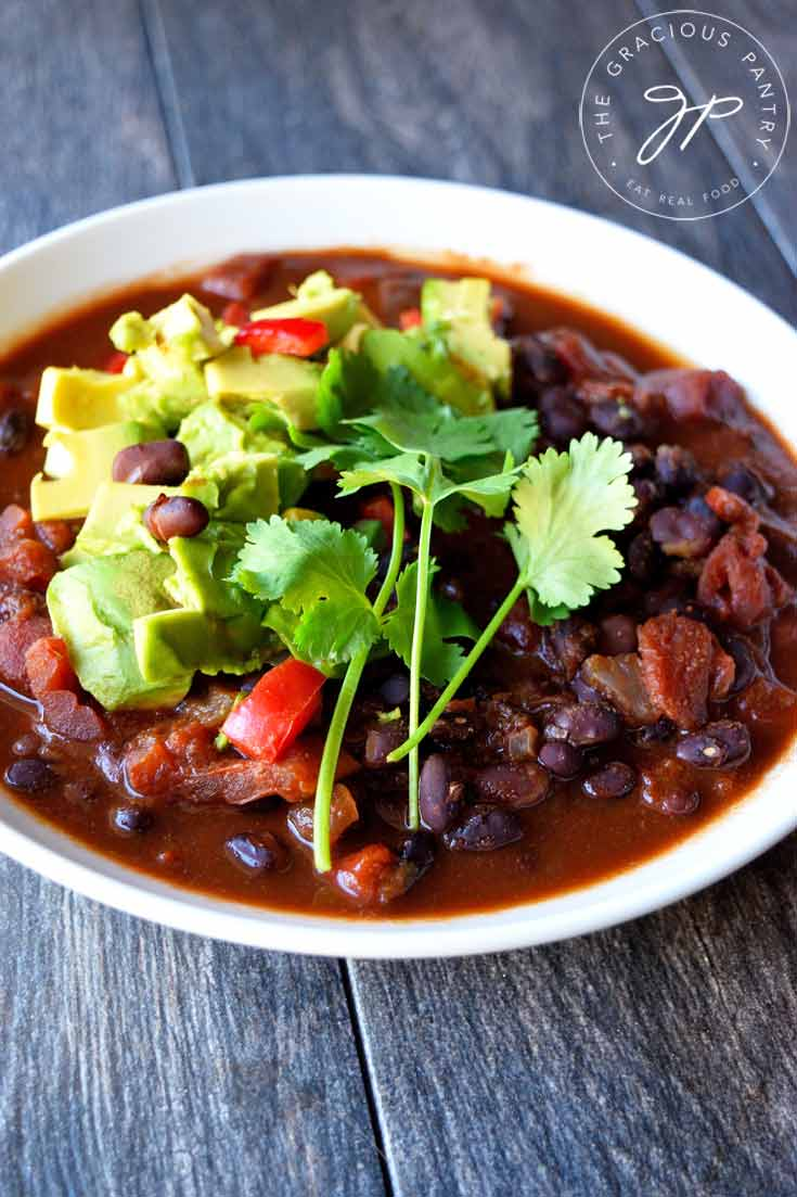 A white bowl filled with this Clean Eating Mexican Black Bean Chili and topped with fresh cilantro and chopped avocado sits on a wooden table, ready to enjoy.